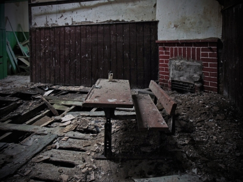 The brickwork fireplace in the smaller classroom at Leitir with an old school desk in the foreground