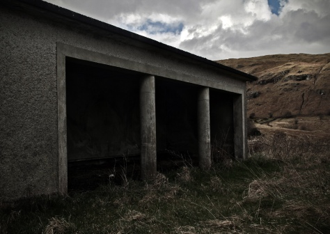 The utilitarian concrete playground shelter of the grassy school yard. Glensaul National School, Greenaun townland, Co. Mayo (c.1950)